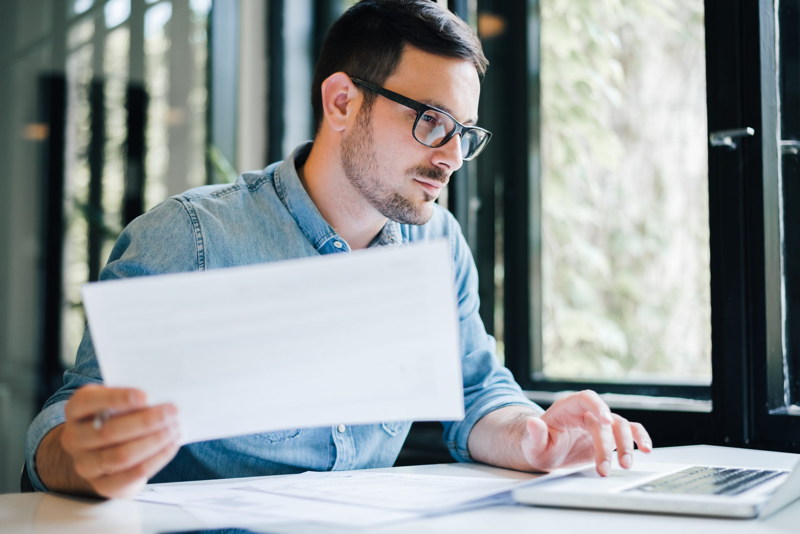 Serious Pensive Thoughtful Focused Young Casual Business Accountant Bookkeeper In Office Looking At And Working With Laptop And Income Tax Return Papers And Documents